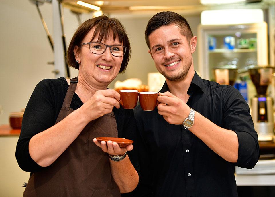 Eine Frau stoßt mit einem Mann mit einem Espresso an