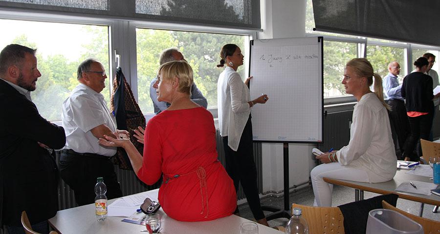 PCC Teilnehmer diskutieren in einem Seminarraum