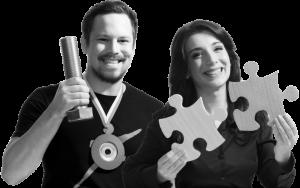 Mann hält übermäßig große Schraube in die Höhe und Frau hält zwei Puzzle-Teile hoch