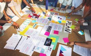 Viele Mitarbeiter stehen um einen Tisch und Brainstormen