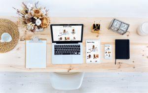 Tisch mit offenen Laptop und einem Notizblog sowie Tablet und Handy daneben