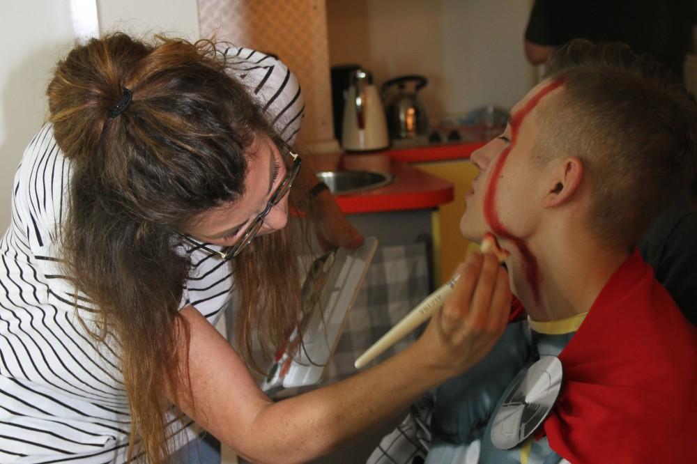 Junger Mann wird von einer Maskenbildnerin für das Shooting geschminkt.
