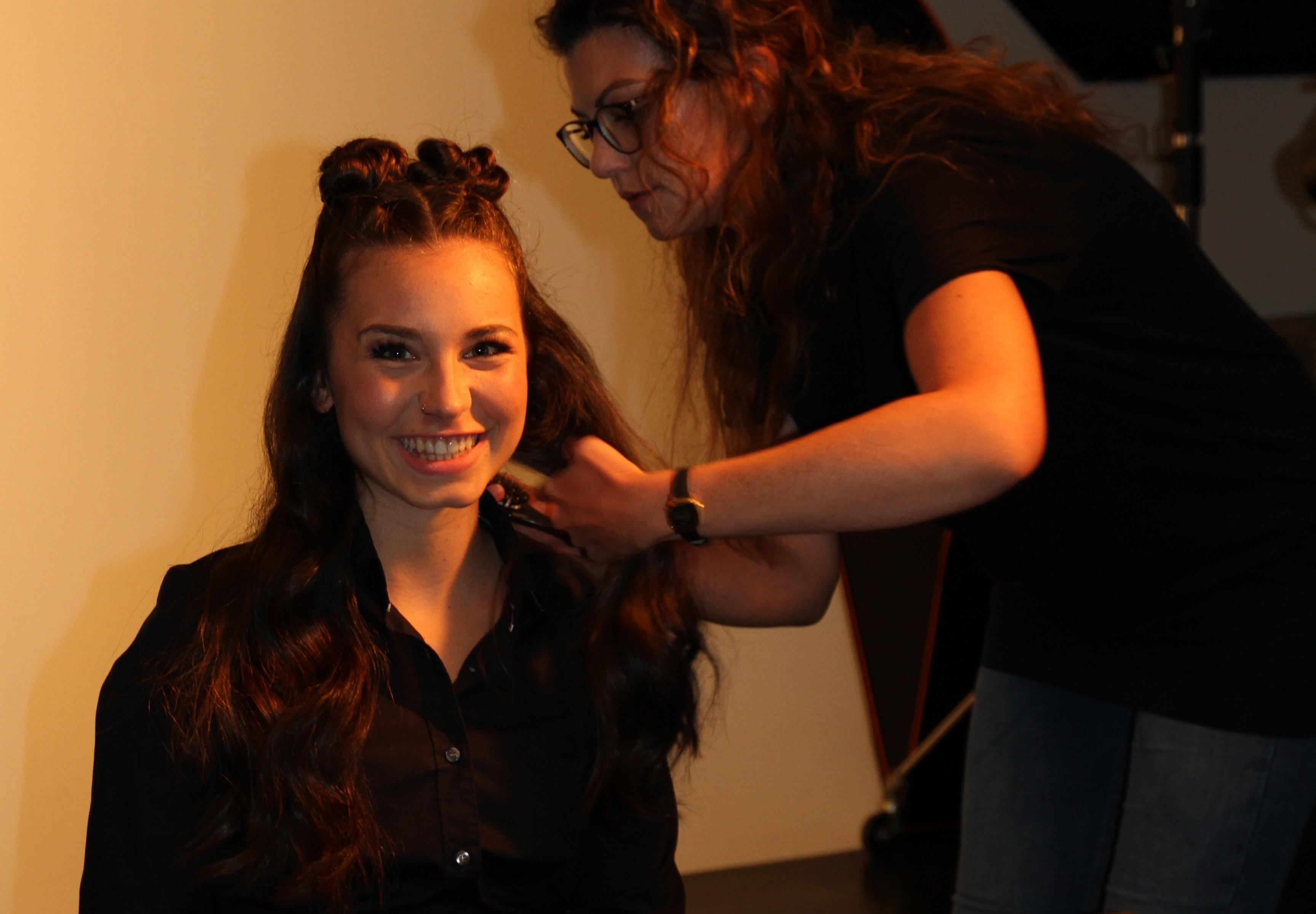 Junge Frau bekommt Haare für das Kampagnenmotiv-Shooting gemacht