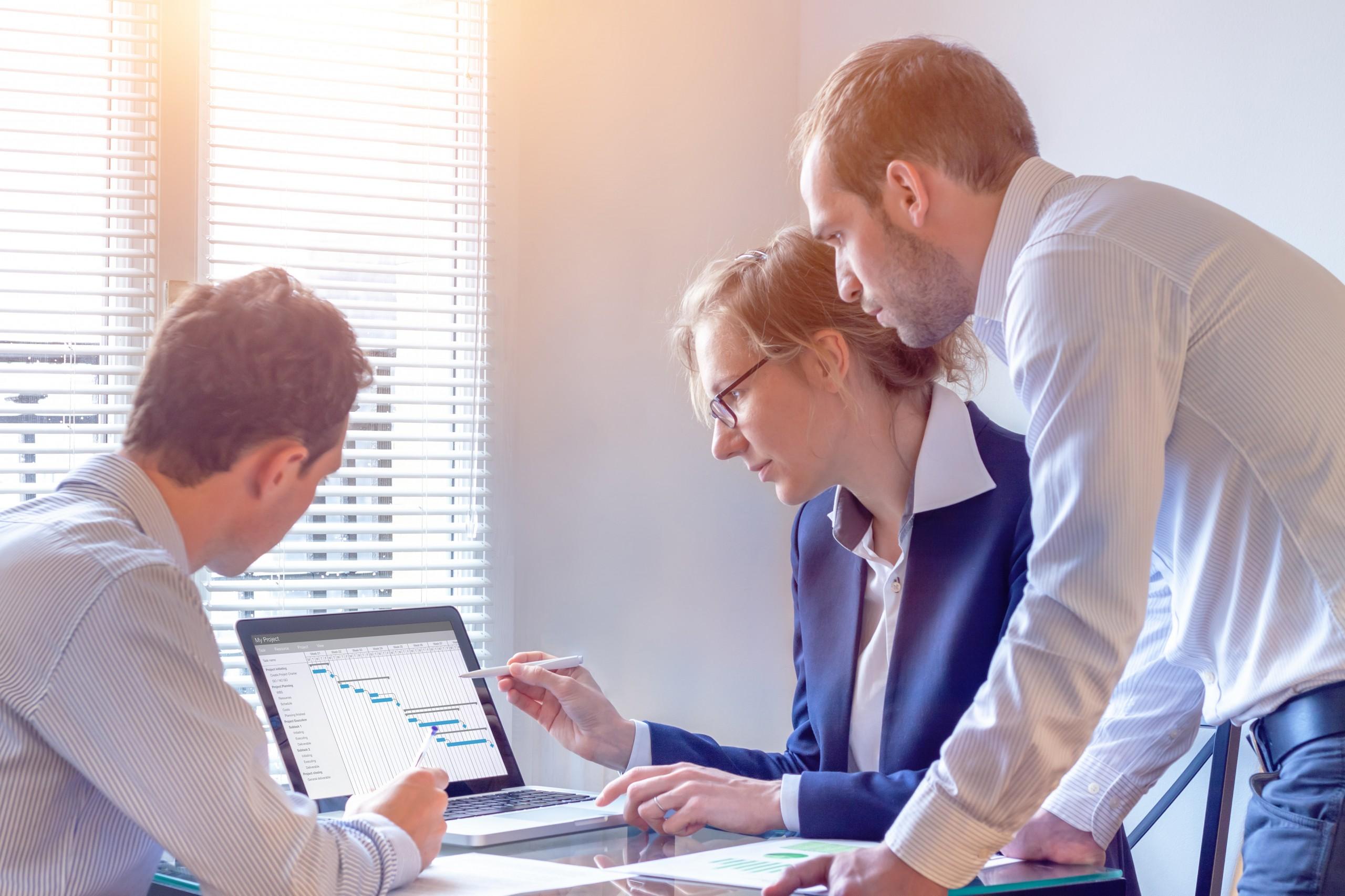 Eine Frau und zwei Männer, die KPI-orientiertes Controlling durchführen.
