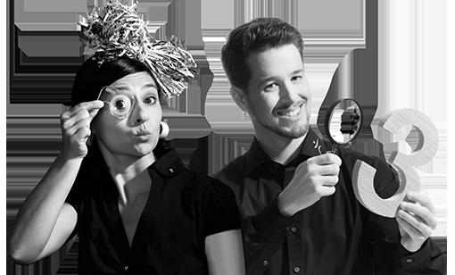 Frau schaut durch eine Tesarolle und Mann hält in der linken Hand eine große drei und in der rechten Hand eine Lupe