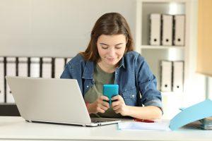 Junge Frau schreibt eine Nachricht in ihr Handy