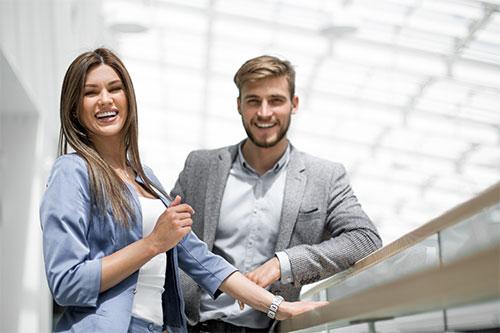 Lachende junge Frau neben einem lächelnden Mann