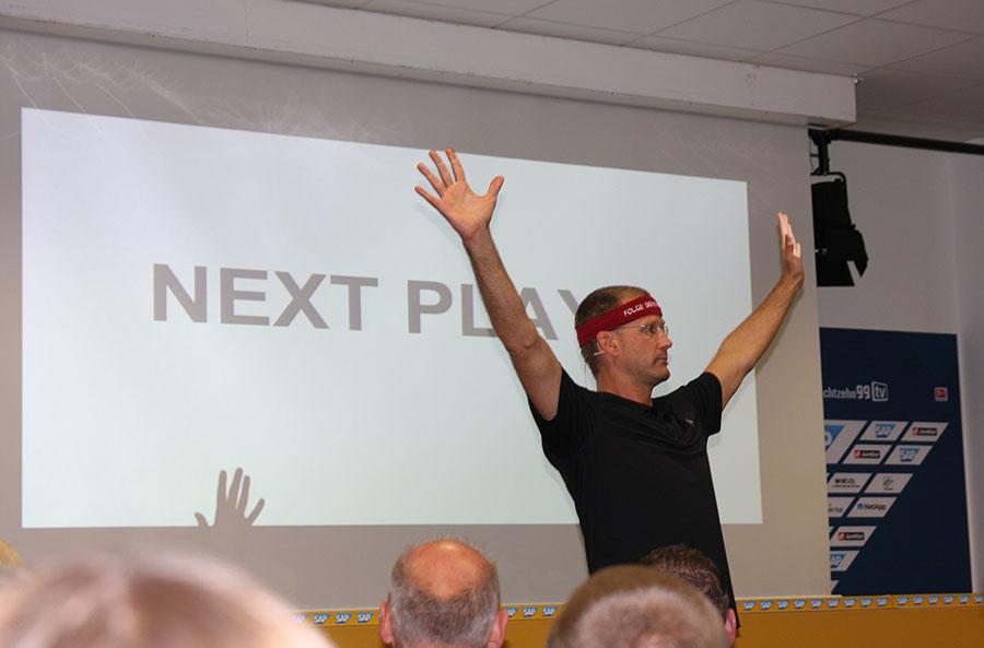 Christian Bischoff hebt die Arme zum Beginn seines Vortrags.