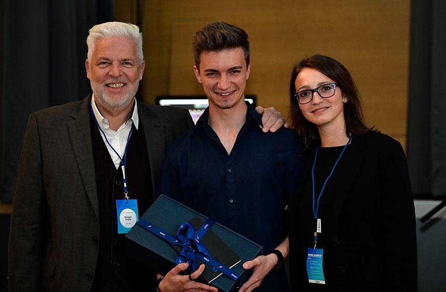 Thomas Noschka steht nach Geschenkübergabe neben Rüdiger Probst und Annabelle Bahm