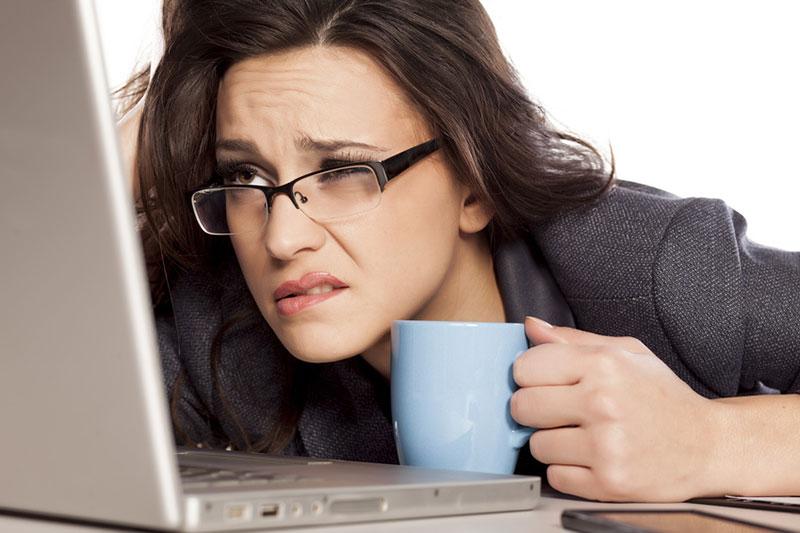 Frau mit Brille stützt den kopf auf dem Tisch auf und blickt verzweifelt in den Laptop