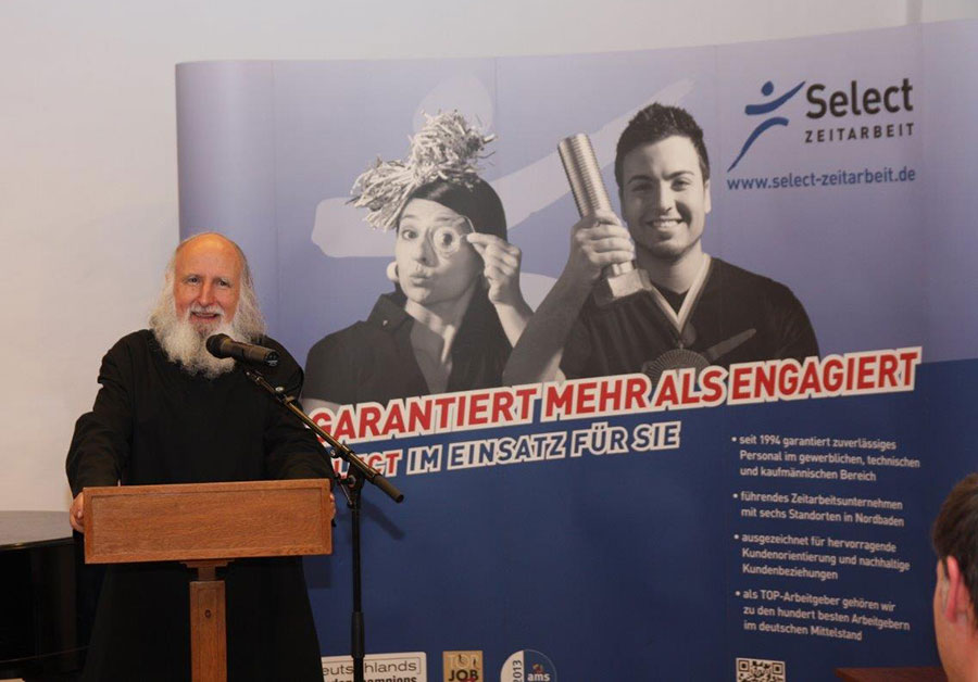 Pater Anselm spricht in ein Mikrofon am Rednerpult
