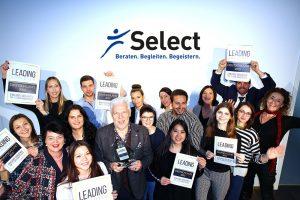 Mitarbeiter der Select GmbH heben die Leading Employer Auszeichnung in die Luft und freuen sich