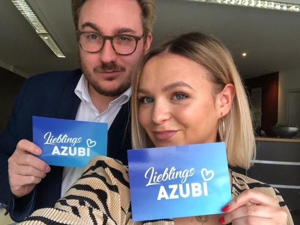 """Azubi Nico und Sina mit einer Postkarte in der Hand auf der """"Lieblingsazubi"""" steht"""