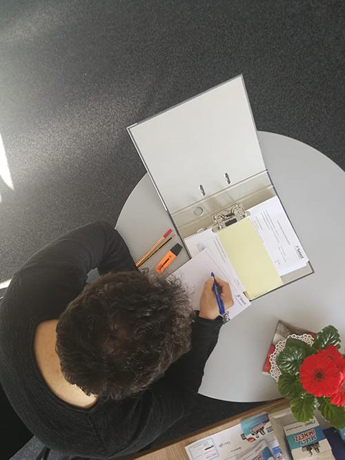 Azubi Hakan bei seinen Schulaufgaben am Schreibtisch