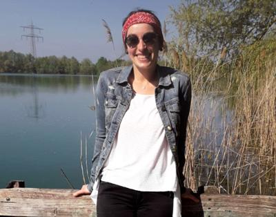 Studierende Selina steht auf einem Steg am See und lacht in die Kamera.